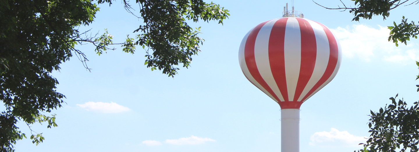 Red and white striped water tower; tree branches surround it