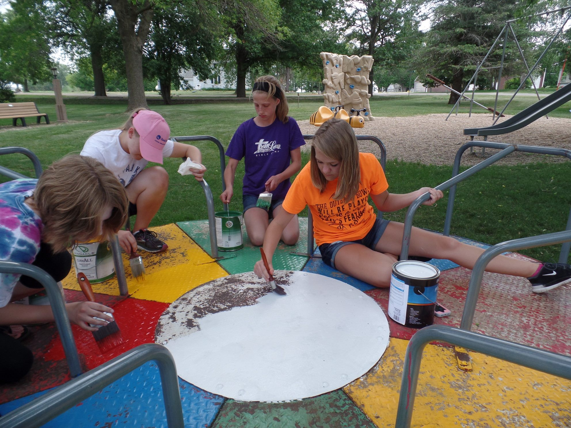 Image of volunteers painting playground equipment at Plover City Park